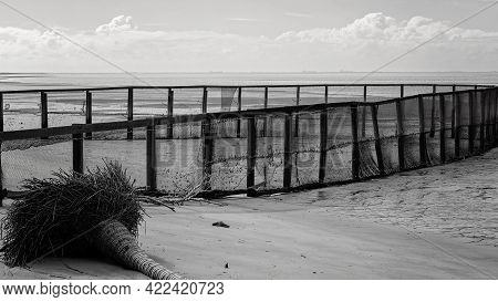 A Netted Safe Swimming Enclosure On A Beach With The Tide Out, Rendered In Monotone