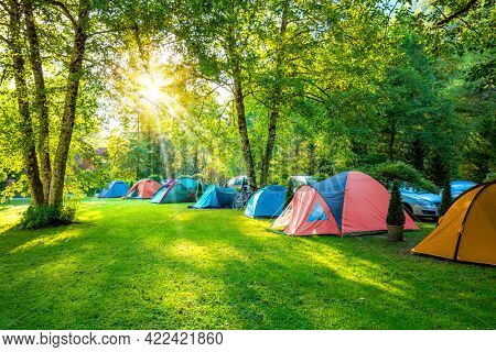 Tents Camping area, early morning. Be Happy!  Natural area with big trees and green grass