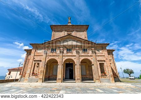 Low angle view of old brick catholic church under blue sky in small town of Diano d'Alba in Piedmont, Northern Italy.