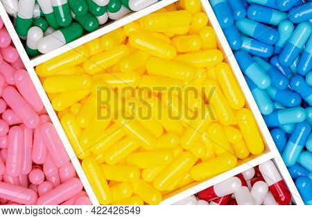 Top View Of Yellow, Blue, Pink, Red, Green, And White Capsule Pills In Plastic Box Texture Backgroun