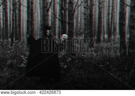 Black Terrible Witch With A Skull In The Hands Of A Dead Man Performs An Occult Mystical Ritual