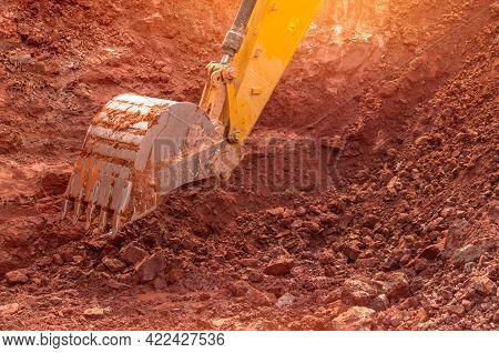 Backhoe Working By Digging Soil At Construction Site. Bucket Of Backhoe Digging Soil. Crawler Excava