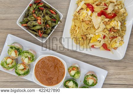 Full Feast Of Spicy Thai Food On The Wooden Table With The Featured Dish Being The Fresh Shriimp Rol