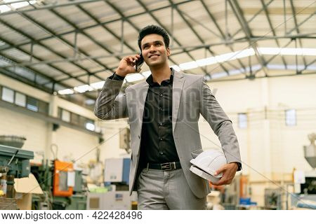 Young Adult 20s Indian Asian Factory Businessman In Formal Suit Walking Talking On The Phone. Confid