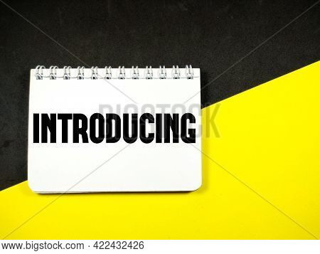 Business Concept. Notebook With Text Introducing On Black And Yellow Background