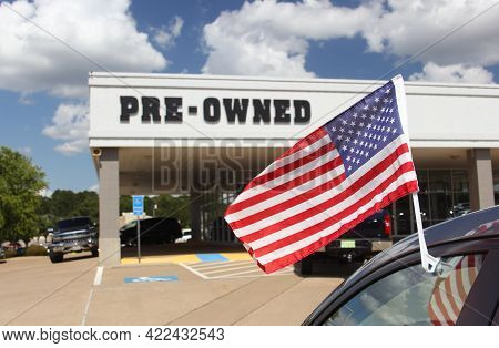 Pre-owned Car Dealership With American Flag And Blue Sky