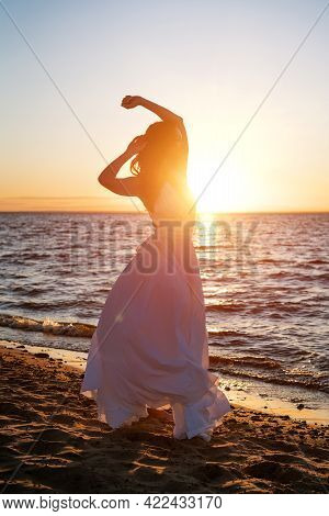 A Beautiful Young Woman Of Caucasian Appearance With Dyed Hair Posing On The Seashore In The Sun At