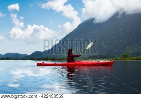 Adventure Caucasian Adult Woman Kayaking In Red Kayak Surrounded By Canadian Mountain Landscape. Blu