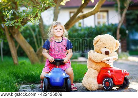 Little Adorable Toddler Girl Driving Toy Car And Having Fun With Playing With Plush Toy Bear, Outdoo