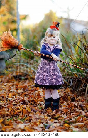 Cute Little Toddler Girl Dressed As A Witch Celebrates Halloween. Happy Child Outdoors, With Orange