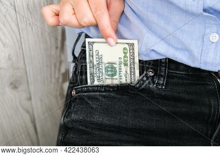 Close Up Hand Of Businesswoman Holding Banknote Into Pocket. Profitable Investment. The Exchange Of