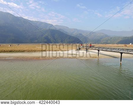 View Landscape Rice Paddy Field And Nepali People Walking On Wooden Bridge Cross Irrigation Reservoi