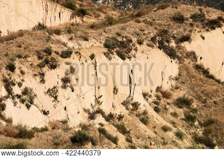 Eroded Sandstone Bluffs On Arid Badlands Covered With Chaparral Shrubs At The Mojave Desert In The C