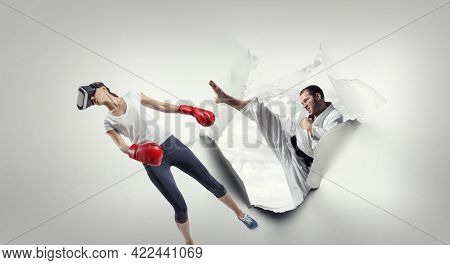 Young woman boxing in VR glasses . Mixed media
