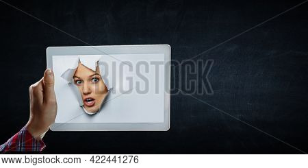 Female face through the hole in paper . Mixed media