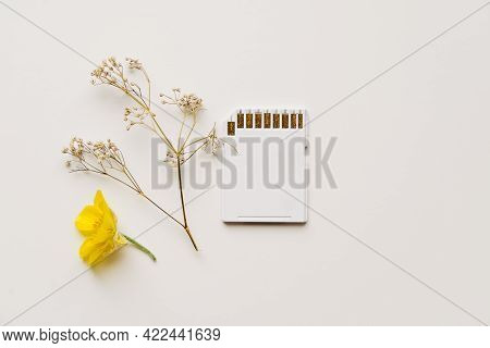 White Memory Card On White Background With Filed Flowers. Eco Friendly Sustainable Technology Concep