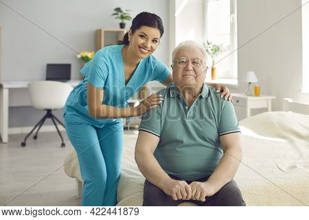 Caring Nurse Hugs Old Man Patient Smiling Looking At Camera During Visit At Home