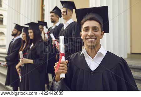 Happy Confident Graduate Guy In A Mantle With A Diploma In His Hands.