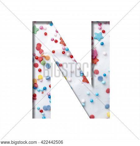 Sweet Glaze Font. The Letter N Cut Out Of Paper On The Background Of White Sweet Glaze With Colored