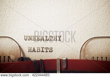 Unhealthy habits phrase written with a typewriter.