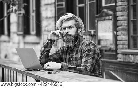 Communication By Video Call. Businessman With Laptop And Phone Sitting In Cafe. Handsome Man Working