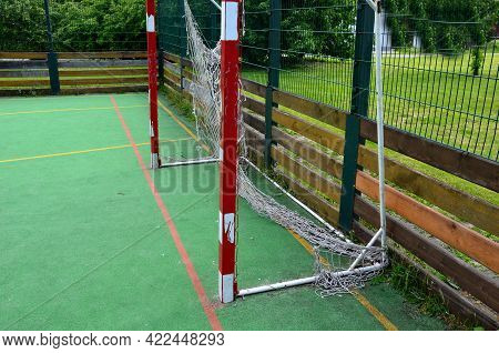 Multifunctional Outdoor Playground For Ball Games At School. Green Artificial Turf From A Plastic Ca