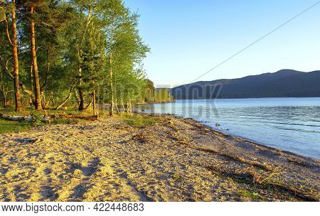 Calm Beautiful Sandy Beach On Lake With Mountains On The Background In The Summertime During The Sun