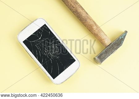 A Cell Phone With Cracked Screen And A Hammer On Brown Background