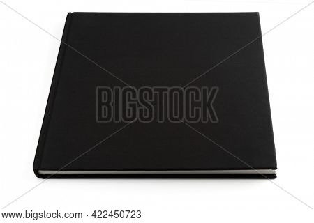 Black book lying on white surface, isolated with smooth shadows