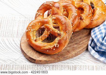Fresh baked homemade pretzel with sea salt on wooden table. Classic beer snack