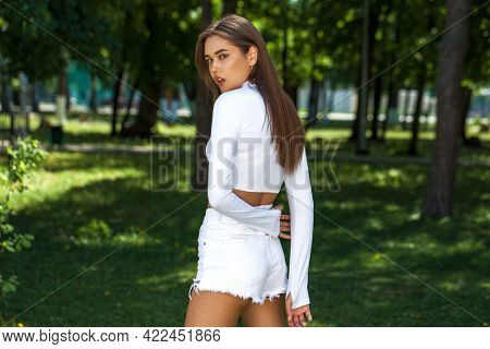 Portrait of a young beautiful girl in white denim shorts posing in a summer park