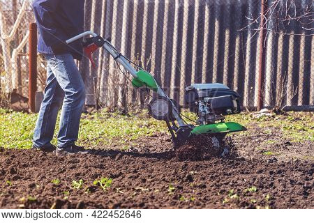 Farmer Man Plows The Land With A Cultivator Preparing The Soil For Sowing.