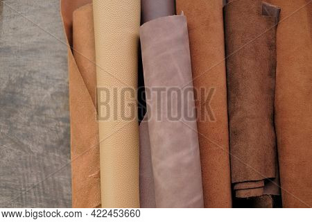 Genuine Leather In Brown And Gray Colors. Leather Pieces Set On A Wooden Table. Leather Industry.lea