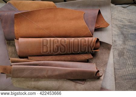 Genuine Leather In Brown And Gray Colors. Leather Pieces Set On A Wooden Table. Leather Industry. Ho