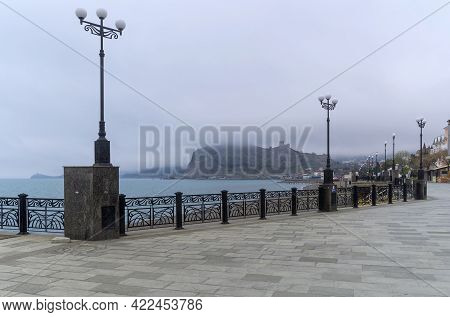 An Empty Embankment In The Small Resort Town Of Sudak, Crimea. End Of April, Overcast, Low Clouds. O