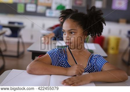 African american girl studying while sitting on her desk in the class at school. school and education concept