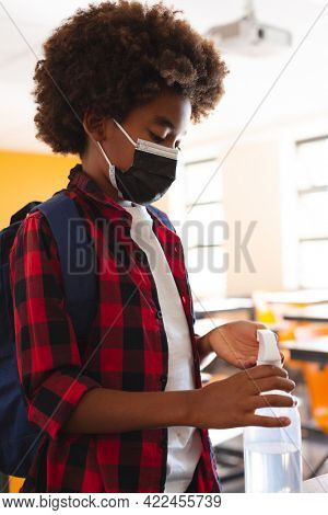 African american schoolboy in face mask standing in classroom disinfecting hands. childhood and education at elementary school during coronavirus covid19 pandemic.