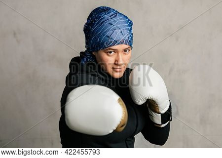 Young Islamic woman wearing a sports hijab while boxing