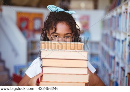 Portrait of happy african american schoolgirl carrying stack of books in school library. childhood and education at elementary school.