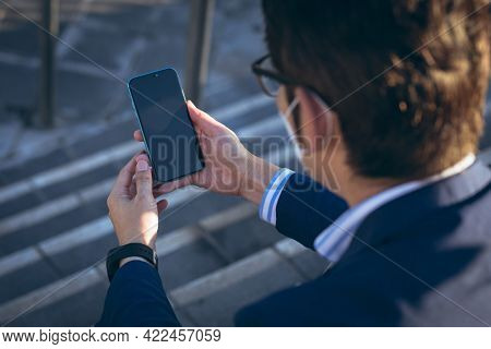 Asian businessman wearing face mask using smartphone sitting on steps in city street. digital nomad out and about in city during covid 19 pandemic concept.