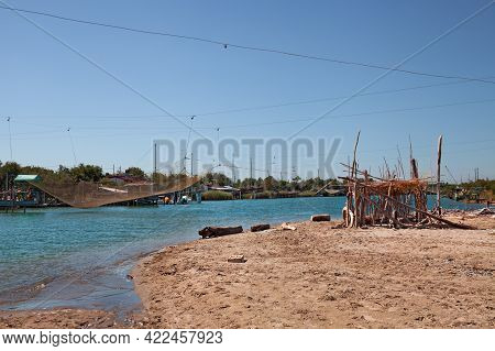 Ravenna, Emilia Romagna, Italy: Landscape Of The River Mouth Fiumi Uniti With Fishing Huts, Nets And