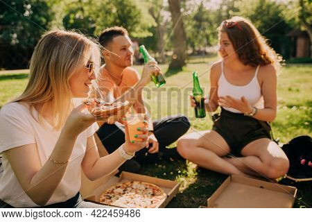 Young blonde girl in sunglassesdrinking alcohol and eating pizza with her friends outdoors.