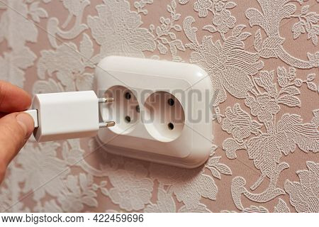 In The Photo, A Man's Hand Inserts The Charger Plug Into The Socket.