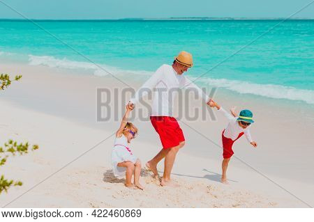 Happy Father With Son And Daughter Play On Beach