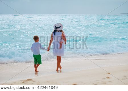 Mother With Son And Daughter Walking On Beach At Sunset