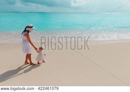 Mother And Little Daughter Walking On Beach