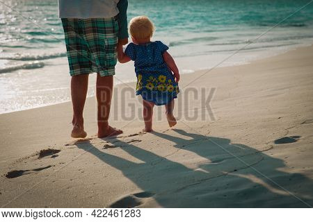 Father And Little Daughter Walk On Sunset Beach