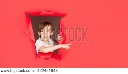Boy In Red Paper Hole Pointing With Finger Aside. Surprised Boy Looking Through Hole In Paper Wall.