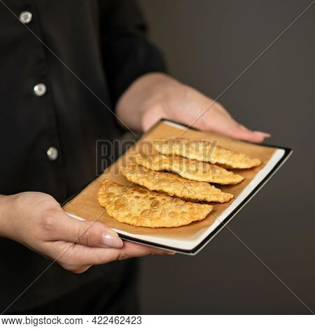 Female Chef Holding Plate Of Freshly-fried Pasties On Parchment Paper. Delicious Cheburek, Crispy Pu