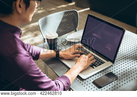 Asian businessman using laptop with blank screen sitting at table in cafe. digital nomad out and about in city concept.